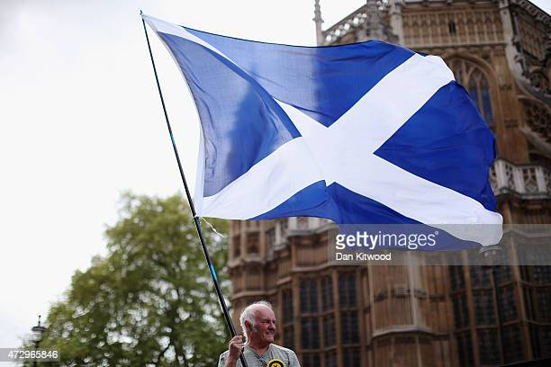 A man waves a Scottish flag outside the Houses of Parliament as First Minister and leader of the SNP Nicola Sturgeon was joined by the newly elected...