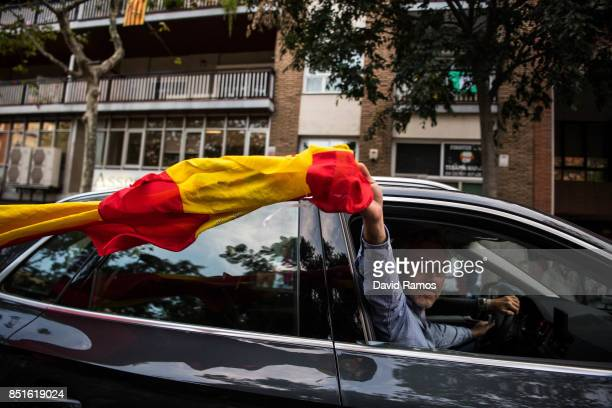 A man waves a Spanish flag as he drives past an Antiseparatist demonstration called by Spanish far right groups on September 22 2017 in Barcelona...
