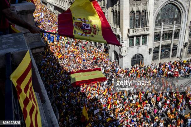 A man waves a Spanish national flag from a balcony as he looks down on demonstrators during a protest for Spanish unity in Barcelona Spain on Sunday...