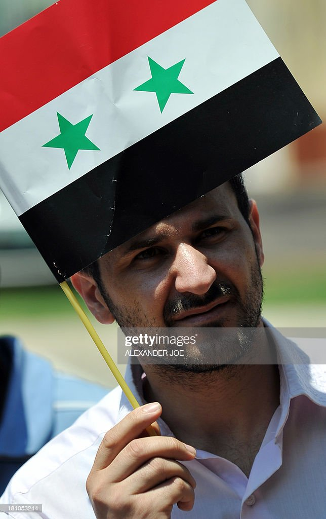 A man waves a Syrian flag as Syrians and members of the Congress of South African Trade Unions (COSATU) gather outside the US embassy in Pretoria on October 11, 2013 during a protest against US intervention in Syria and the conflict in the war-torn country which they consider to be 'in the interest of imperialism'.