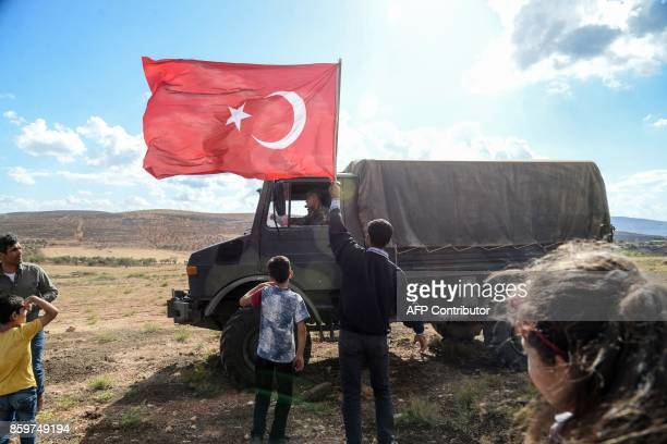A man waves a Turkish national flag as a Turkish army vehicle drives past during a demonstration in support of the Turkish army's Idlib operation...
