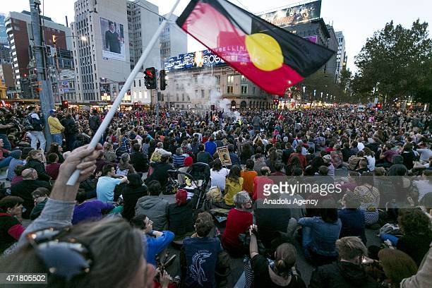 A man waves an Aboriginal flag as an estimated crowd of 10000 people gather during a rally protesting against the forced closure of Aboriginal...