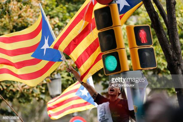 A man waves an 'Esteladas' during a protest in front of the Economy headquarters of Catalonia's regional government in Barcelona on September 20 2017...