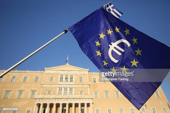 A man waves an EU flag with the euro currency symbol in front to of the Greek Parliament during a pro European rally on July 9 2015 in Athens Greece...