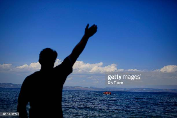 A man waves as refugees come ashore near the village of Skala Sikamineas on September 8 2015 in Lesbos Greece More than 230000 people have landed on...