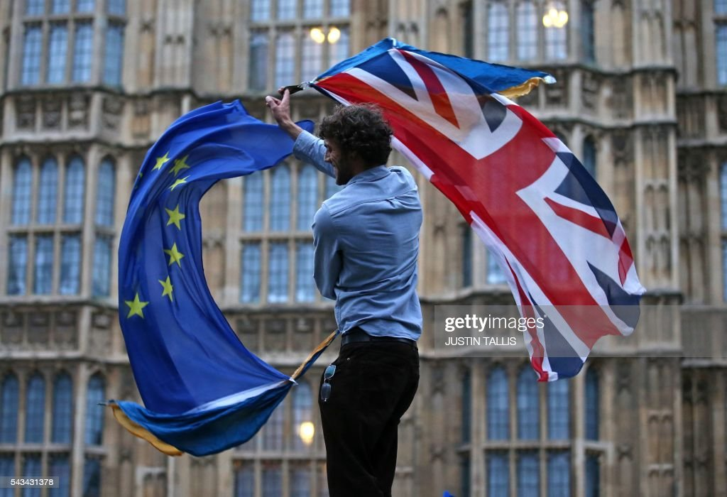 A man waves both a Union flag and a European flag together on College Green outside The Houses of Parliament at an anti-Brexit protest in central London on June 28, 2016. EU leaders attempted to rescue the European project and Prime Minister David Cameron sought to calm fears over Britain's vote to leave the bloc as ratings agencies downgraded the country. Britain has been pitched into uncertainty by the June 23 referendum result, with Cameron announcing his resignation, the economy facing a string of shocks and Scotland making a fresh threat to break away. / AFP / JUSTIN