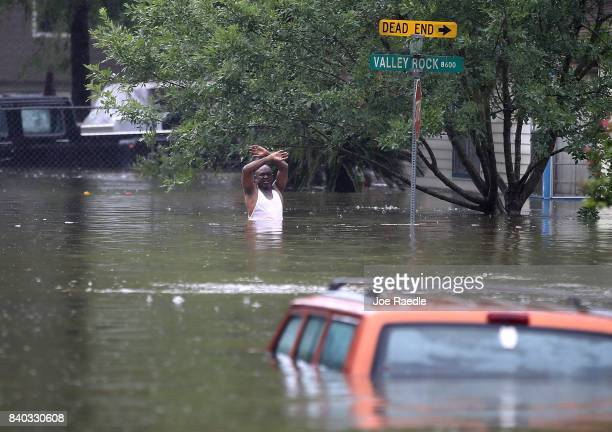 A man waves down a rescue crew as he tries to leave the area after it was inundated with flooding from Hurricane Harvey on August 28 2017 in Houston...
