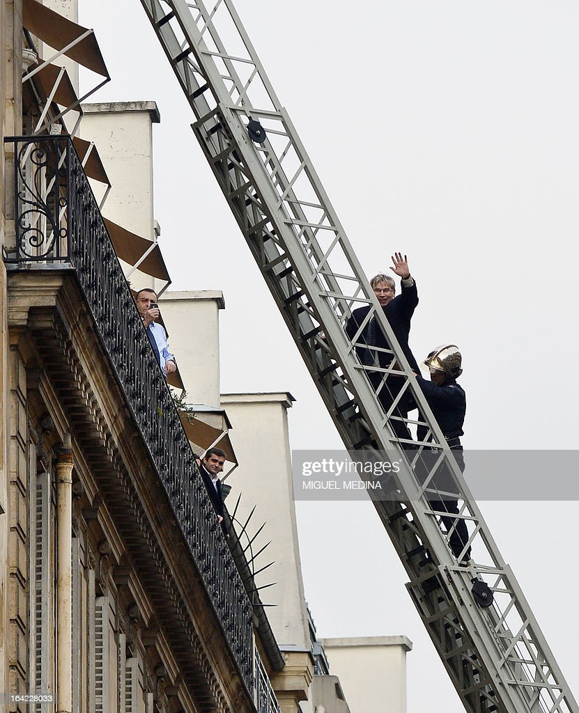 A man (C) waves during his evacuation by firemen after succeededing to reach, on March 21, 2013, the roof of the US embassy in Paris in spite of tough security measures. The man, Herve Couasnon, 54, a bus driver from Perigueux, southwestern France, asked to have a meeting with US President Barack Obama, who is today in an official visit in Ramallah, to handle him his CV and speak about peace. The man, succeeded twice in the recent years, to circumvent security measures in France. AFP PHOTO MIGUEL MEDINA