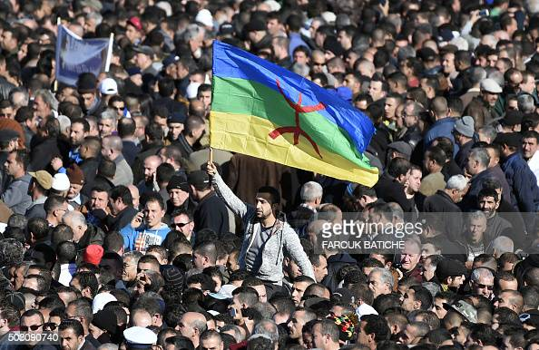A man waves the Amazigh flag as thousands of mourners attend the funeral procession and burial of Hocine AitAhmed one of the fathers of Algeria's...