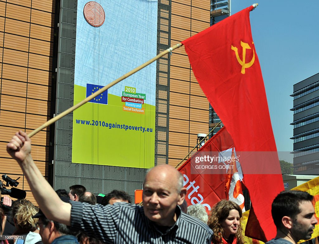 A man waves the communist red flag during a demonstration in solidarity with the Greek workers in front of the EU Commission building on May 20, 2010 in Brussels. Meanwhile, more than 20,000 Greeks took to the streets of Athens and second city Thessaloniki on Thursday in a new general strike against the government's debt-dictated austerity spending cuts and pension reform.