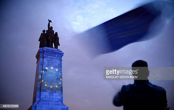 A man waves the EU flag while the Soviet Army monument is illuminated with the European Union symbol during a preelection meeting of the Reformers...