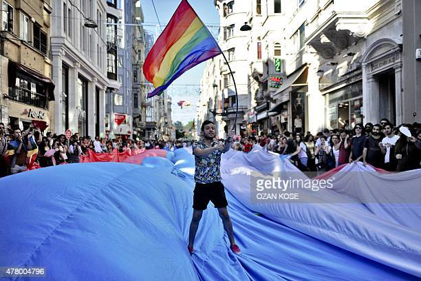 A man waves the gay rainbow flag as he stands on a giant transgender flag during Trans Pride march along Istikbal Avenue in Istanbul on June 21 2015...