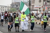 A man waves the Nigerian flag above his head during the Access Bank Lagos City Marathon on February 6 2016 The Lagos City Marathon is one of the...