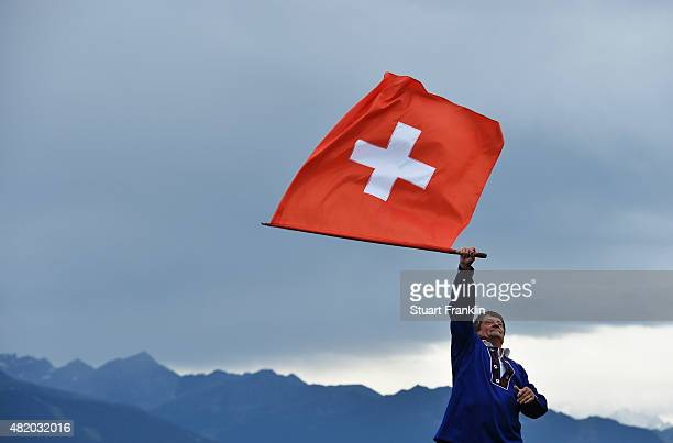 A man waves the Swiss flag during the final round of the Omega European Masters at CranssurSierre Golf Club on July 26 2015 in CransMontana...