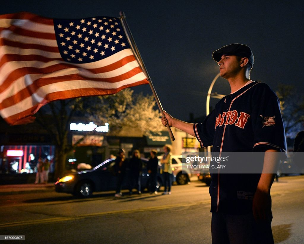 A man waves the US flag after the capture of the second of two suspects wanted in the Boston Marathon bombings April 19, 2013 in Watertown, Massachusetts. Thousands of heavily armed police staged an intense manhunt Friday for a Chechen teenager suspected in the Boston marathon bombings with his brother, who was killed in a shootout. Dzhokhar Tsarnaev, 19, defied the massive force after his 26-year-old brother Tamerlan was shot and suffered critical injuries from explosives believed to have been strapped to his body.