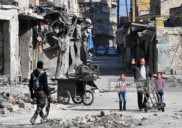 TOPSHOT A man waves to a member of the Syrian progovernment forces patrolling a street in the newly retaken Bab alHadid neighbourhood in Aleppo's Old...