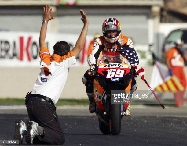 A man waves to Nicky Hayden of the US as he clinches the World MotoGP title after finishing third in the MotoGP race in the Ricardo Torma racetrack...