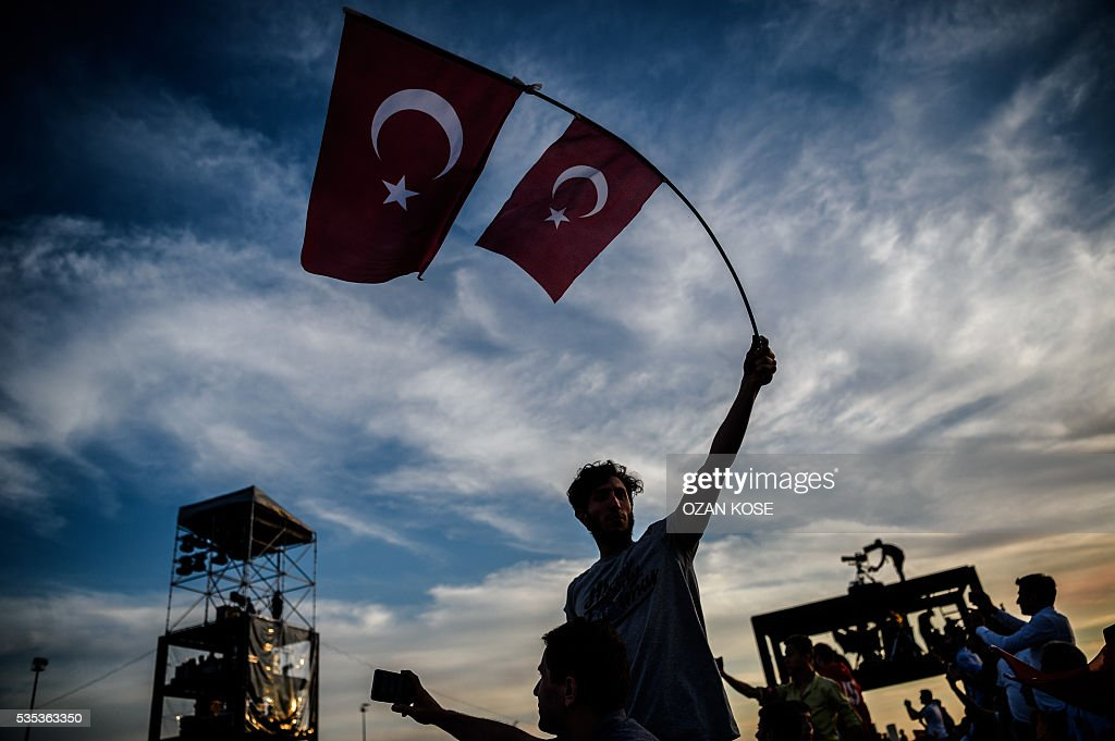 A man waves Turkish national flags as Turkish President speaks during a rally to mark the 563rd anniversary of the conquest of Istanbul by Ottoman Turks on May 29, 2016 in Istanbul. / AFP / OZAN