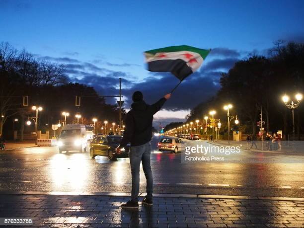 Man waving a Syrian flag in the street Syrian migrants living in Berlin held a demonstration at Brandenburg Gate asking Russian president Vladimir...