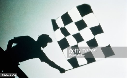 Man waving checkered flag at motor race, (B&W)