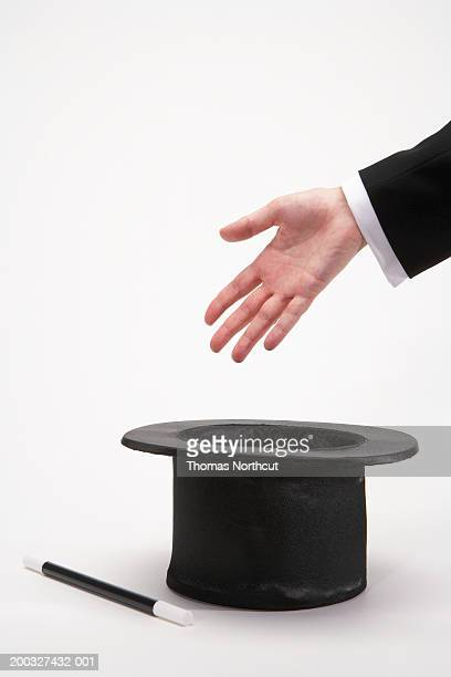 Man waving hand over top hat and magic wand, close-up of hand