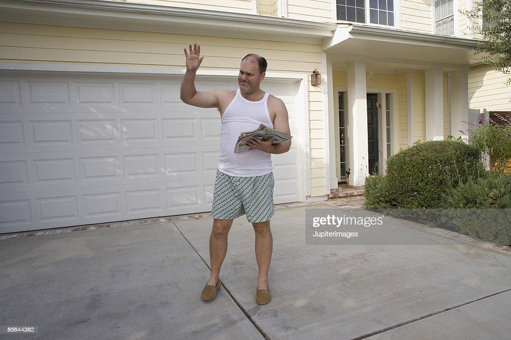 Man waving outside of home