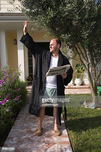 Man waving outside of home
