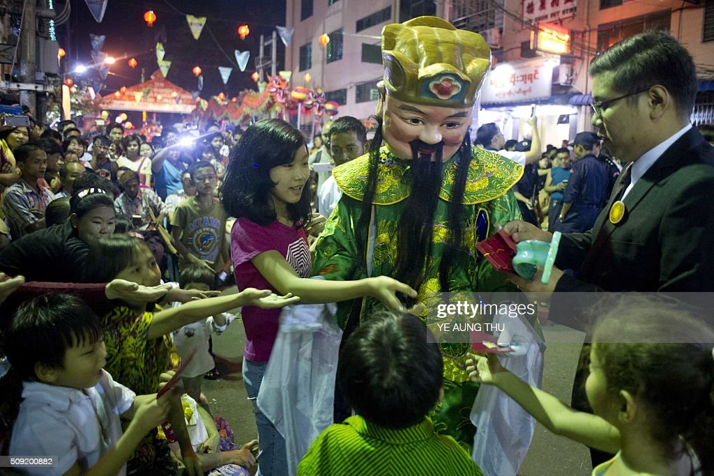 A man wear chinese spirit dress during the Chinese traditional dragon and lion dance competition to mark Chinese Lunar New Year or Spring Festival in Latha township, Yangon's Chinatown district on February 9, 2016. Lunar New Year which marks the start of the year of the monkey. / AFP / YE AUNG THU