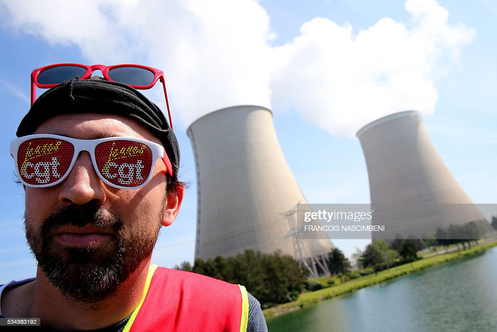A man wear glasses embossed with the CGT union logo rallies outside the nuclear power plant of Nogent-sur-Marne, eastern suburbs of Paris on May 26, 2016, during a protest against controversial labour market reforms that has already severely disrupted fuel supplies. With two weeks until France hosts the Euro 2016 football championships, the country has been paralysed by a series of transport strikes and fuel shortages that has heaped pressure on the deeply unpopular Socialist government. / AFP / FRANCOIS