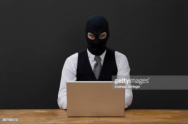 A man wearing a  balaclava and using a laptop