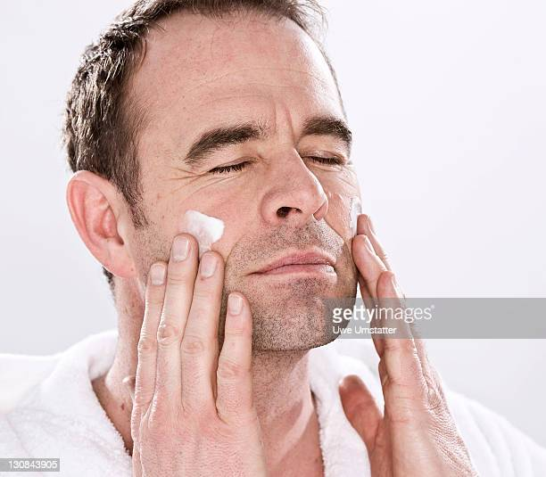 Man wearing a bathrobe, relaxed, putting lotion on his face