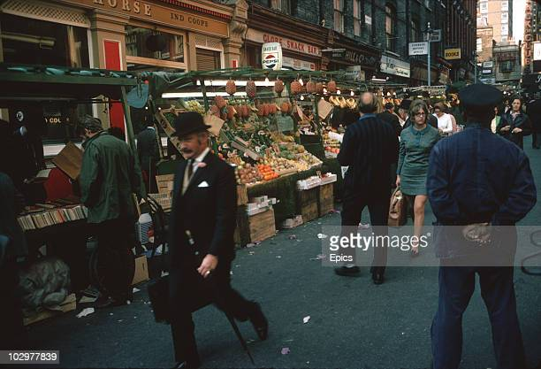 A man wearing a bowler hat and carrying an umbrella walks past fruit and vegetable market stalls in Soho London October 1970