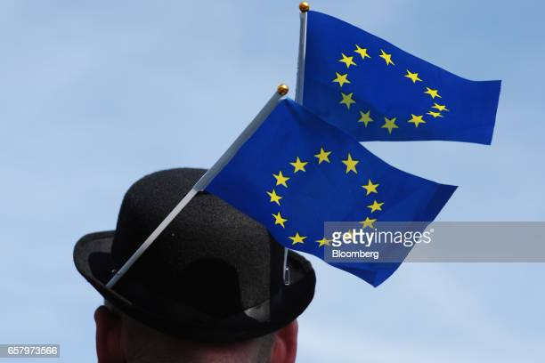 A man wearing a bowler hat with two European Union flags pinned to it joins protesters during a Unite for Europe march to protest Brexit in central...