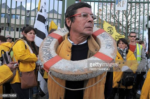 A man wearing a buoy around his neck stands with others in yellow cires on November 18 2014 in Vannes western France as they take part in a...