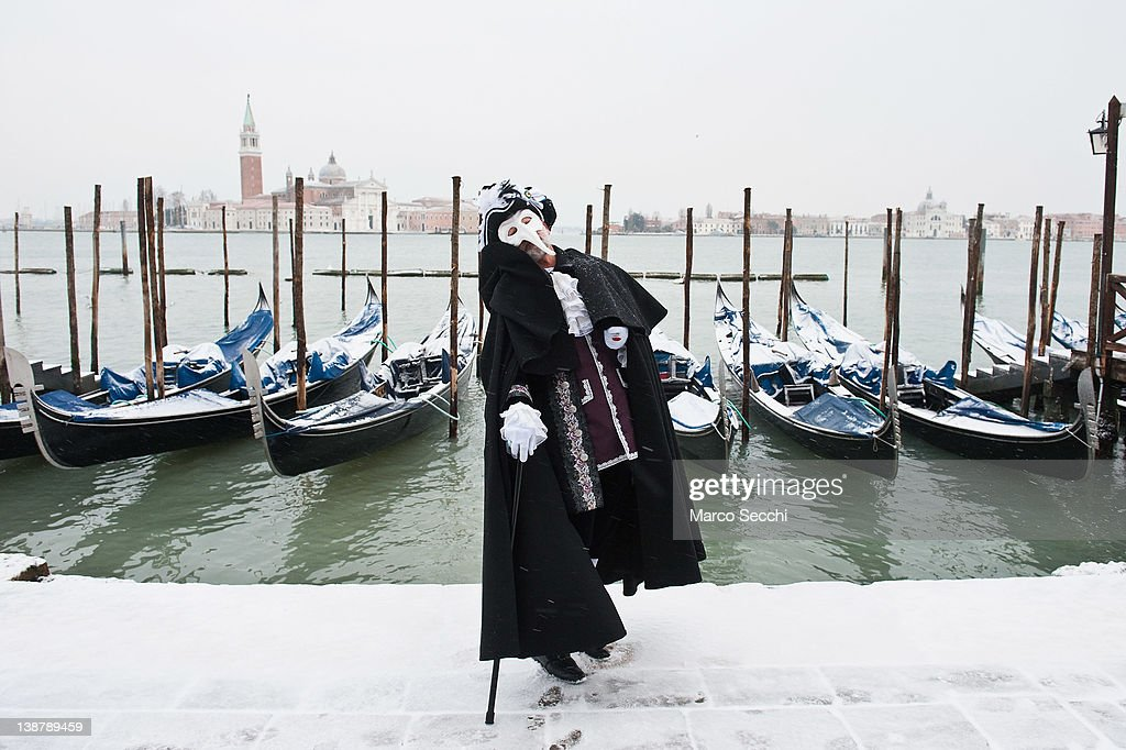 A man wearing a Canival costume poses for pictures in the snow in St Mark's Square on February 12, 2012 in Venice, Italy. Italy, like most of Europe, is experiencing freezing temperatures, with the Venice Lagoon freeezing for the first time in over 20 years.
