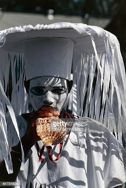 A man wearing a carnival mask and playing a shell Grenada Lesser Antilles