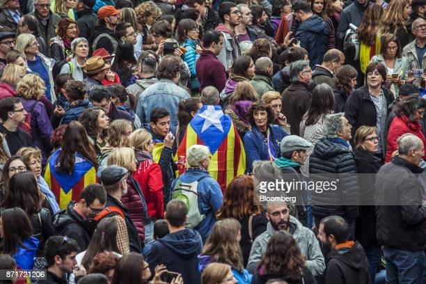 A man wearing a Catalan Estelada flag stands among protesters outside the Generalitat regional government offices in Sant Jaume square calling for...
