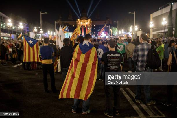 A man wearing a Catalan flag takes listen to speeches during the final proindependence rally at Plaza Espana ahead of Sunday's referendum vote on...