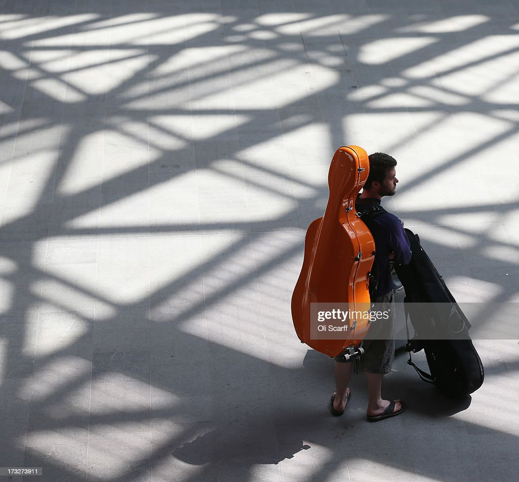 A man wearing a cello case on his back waits for a train in Kings Cross station on July 10, 2013 in London, England.