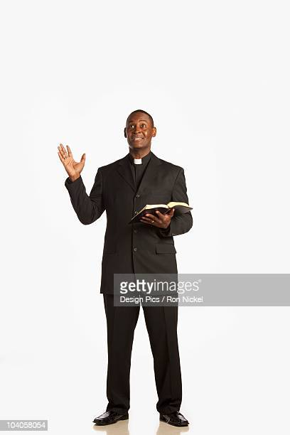 A Man Wearing A Clerical Collar And Preaching From The Bible