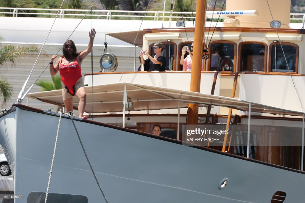 A man wearing a costume waves from a boat as people watch the arrival of the first 'Riviera Water Bike Challenge', a water bike race between Nice and Monaco, in Monaco, on June 4, 2017. /