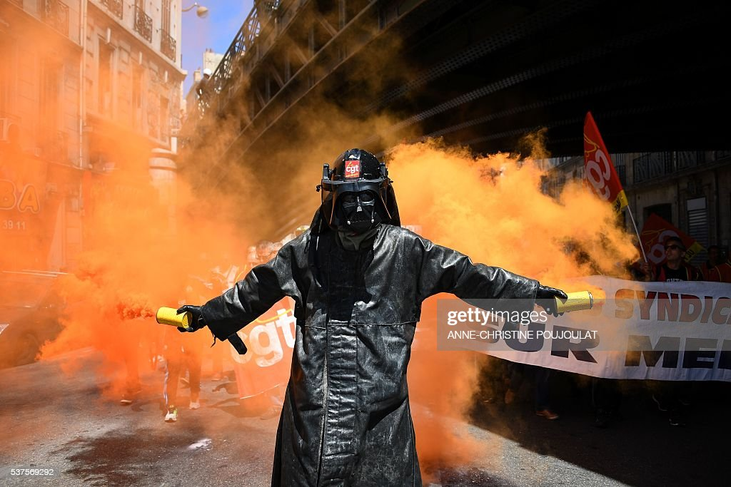 TOPSHOT A man wearing a Dark Vador mask holds smoke flares during a demonstration against the French government's planned labour law reforms on June...