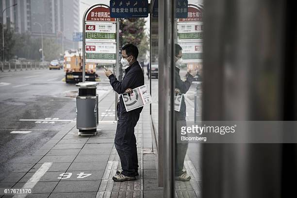 A man wearing a face mask uses a smartphone at a bus station in Beijing China on Wednesday Oct 19 2016 This year's full meeting of the party's...
