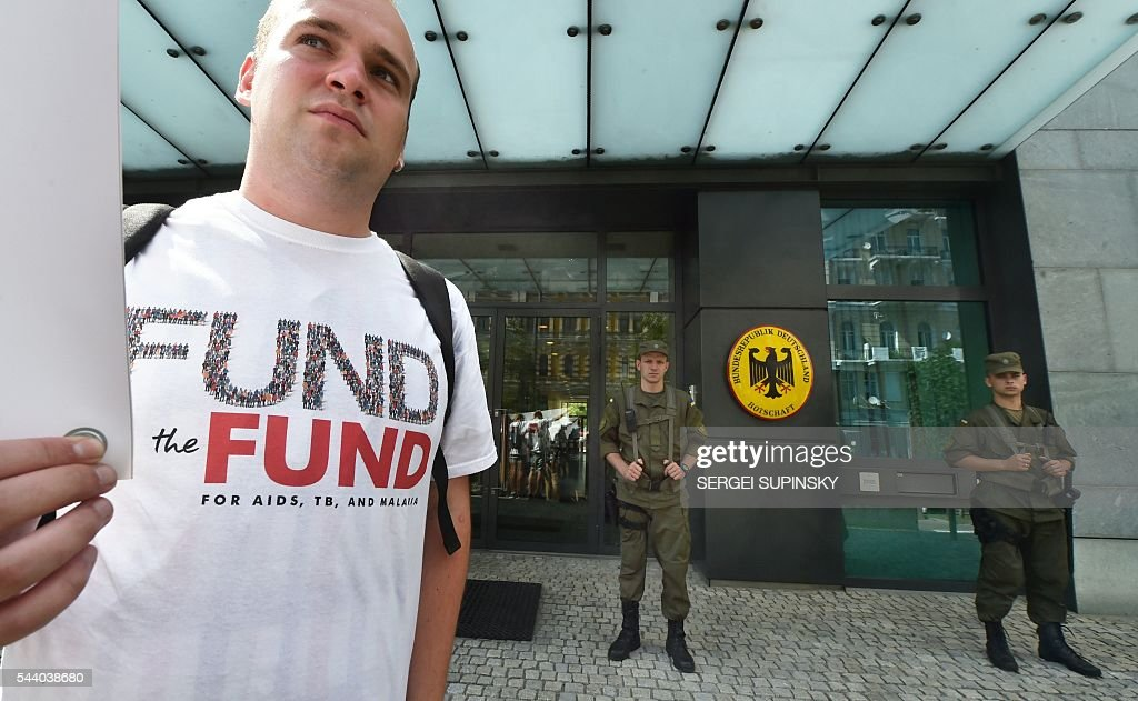 A man wearing a 'Fund the fund' organisation's T-shirt stands in front of German embassy in Kiev on July 1, 2016 during a demonstration called by the international organisation aimed at increasing donor countries funding for programs to fight HIV / AIDS and tuberculosis. / AFP / SERGEI