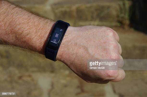 Man wearing a Garmin vivosmart HR smart activity tracker that shows the equivalent of 86 floors climbed after he has walked up Mount Ainslie in...