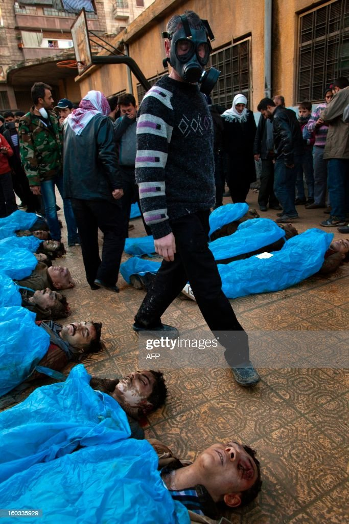 A man wearing a gas mask looks for his relatives amongst the bodies Syrian civilians executed and dumped in the Quweiq river lays in the grounds of the courtyard of a Yarmouk School, in the Bustan al-Qasr district of Aleppo, on January 29, 2013. The bodies of at least 65 young men, all executed with a single gunshot to the head or neck, were found in a river in Aleppo city, adding to the grim list of massacres committed during Syria's 22-month conflict.