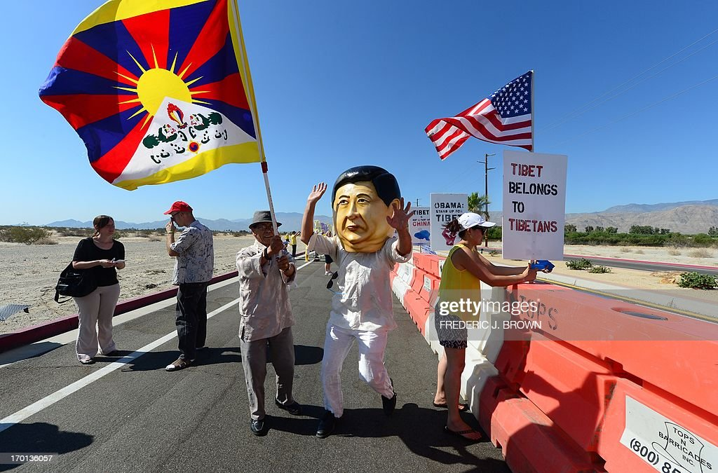 A man wearing a giant head resembling visiting Chinese leader Xi Jinping tries to run from a flag waving protester for the Tibetan cause in a cordoned off protest zone across from where President Barack Obama is due to meet his Chinese counterpart Xi Jinping in the California desert community of Rancho Mirage, a little over 100 hundred miles east of Los Angeles, on June 7, 2013, where they were joined by Falun Gong practioners in protesting the brutal repression of China's ruling Communist Party. Xi, the Chinese leader arrived in southern California the previous evening and stayed in a nearby hotel, according to the local Desert Sun newspaper, ahead of what was planned as an unusually relaxed US-China summit. AFP PHOTO/Federic J. BROWN