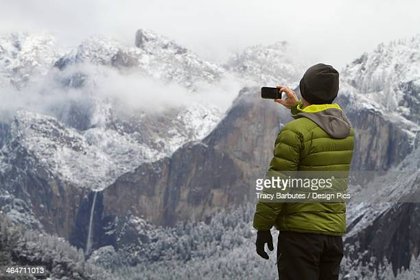 Man wearing a green down jacket as seen from the back taking a picture of yosemite valley and bridal veil falls