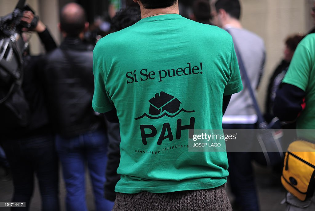 A man wearing a green tshirt reading 'Yes we can' take part in a protest by Platform for Mortgage Victims (PAH) to push for a new law to end a wave of evictions of homeowners ruined by the economic crisis, in Barcelona, on March 27, 2013. AFP PHOTO/ JOSEP LAGO