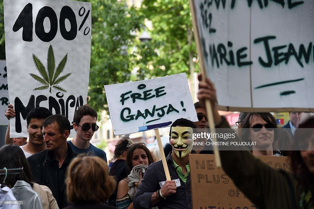 A man wearing a Guy Fawkes mask holds a placard reading 'Free Ganja' during a protest to call for the legalization of marijuana on May 10, 2014, at the Old Harbour in Marseille, southern France. About 147 million people globally -- or about 2.5 percent of the population -- use cannabis, according to the World Health Organization.